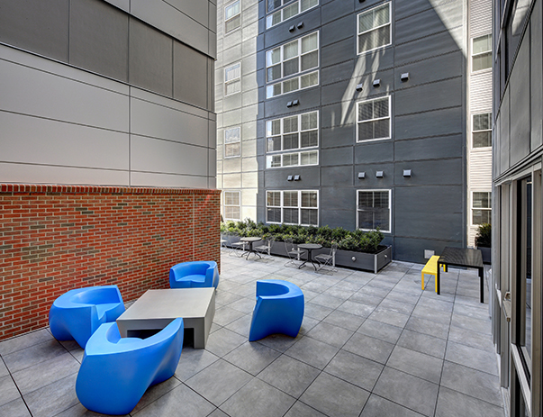 Open-air courtyard lounge with fire table at The Suites at Third near UIUC